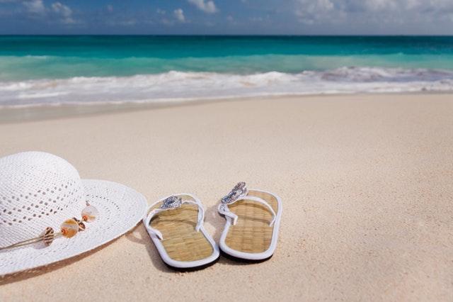 šľapky a klobúk na pláži