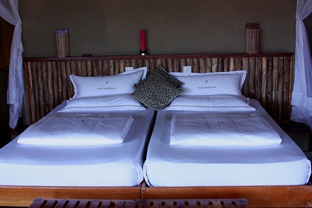 Posteľ s dvoma bielymi matracmi a vankúšmi.jpg